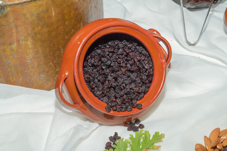 booster: Jar with black sun raisings, high protein high energy health booster food, on a table.