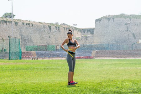 waistline: Female water sprinkled wet athlete woman in sportswear measuring her waistline, hips and chest after a workout at an outdoor field stadium. Healthy lifestyle and sports concept.