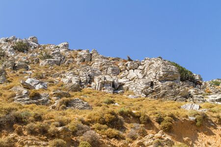 Layered folded rocks formation on southern Crete coast, Greece Stock Photo