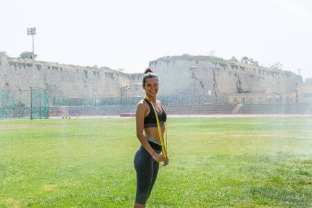 waistline: Female water sprinkled wet athlete woman in sportswear measuring her waistline, hips and chest after a workout at an outdoor field stadium. Healthy lifestyle sports and fitness concept. Stock Photo