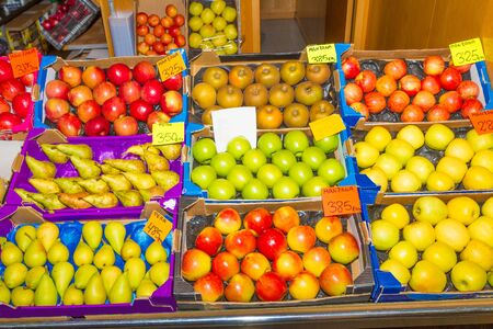 Baskets with varieties of fresh harvest pears and apples on display for sale in a fruit market. Health care and nutrition concept. Stockfoto