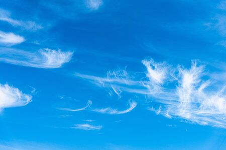 Panoramic view of blue sky with sparse thin swirls of white delicate near transparent clouds
