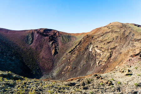 Unique panoramic view of spectacular corrosioned lava ground layers of huge volcano cone. Timanfaya volcanoes park, Lanzarote, Canary Islands, Spain.