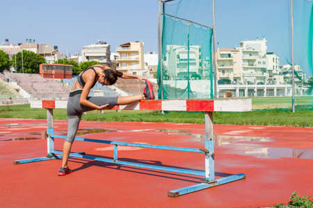 Young woman doing fitness training in local sports stadium outdoors.