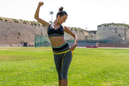 Female water sprinkled athlete in sportswear measuring waistline and hips