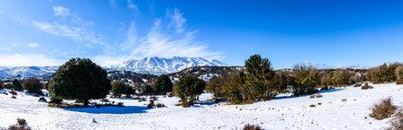 Panoramic winter wonderland high mountain hiking tour, snow-capped mountain rocky ridge peaks in blue sky. Mediterranean trekking adventure Psiloritis mountain range in Crete, Greece.