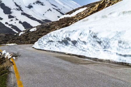 Mountains road wonderland, stunning steep slopes, cliffs and snow-capped rocky peaks
