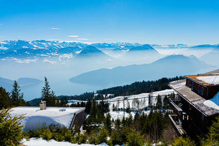 Majestic unique misty blue alpine skyline aerial view panorama of iced Swiss Alps and blue sky. Mount Rigi Switzerland.