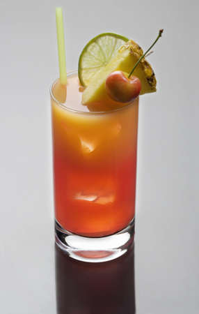 Mai Tai mixed drink with  fruit garnish on a plain grey background with reflection photo