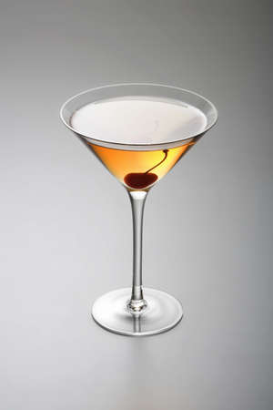 manhattan: Rob Roy or Manhattan mixed drink  with cherry garnish  on grey background