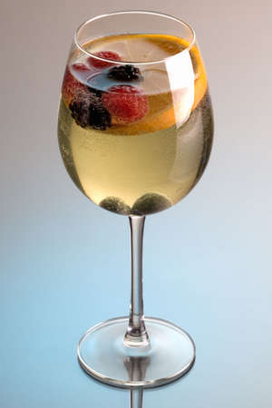 Glass of white wine sangria on grey background with reflection