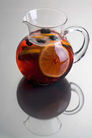 Pitcher of Red Sangria with aranges and blackberries on grey background close up