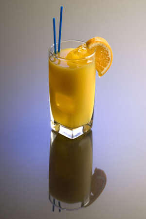 alcohol screwdriver: Screwdriver cocktail with orange garnish on plain background with reflection