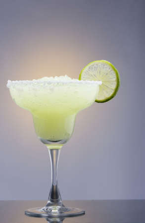 Frozen Margarita mixed drink with lime slice on plain background close up photo