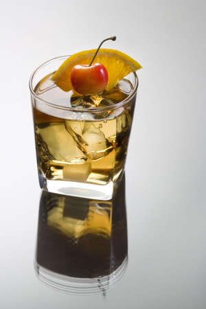 alcoholic drink: Old Fashioned mixed drink with orange slice, cherry and sugar cube garnish on grey background with reflection Stock Photo