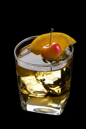 alcoholic: Old Fashioned mixed drink with orange slice, cherry and sugar cube garnish on black background with