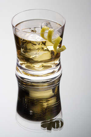 rusty nail: Rusty nail mixed drink with lemon peel on a grey background with reflection