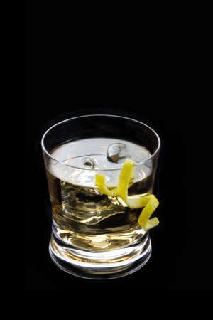 rusty nail: Rusty nail mixed drink with lemon peel on a black background