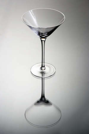 Empty martini glass on a grey background with reflection Stok Fotoğraf