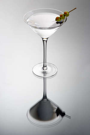 Martini mixed drink with olive garnish on a light grey background with reflection