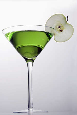 Apple Martini mixed drink with apple slice garnish on grey background photo