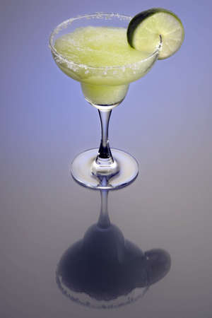 Frozen Margarita mixed drink with lime slice garnish on plain background with reflection Фото со стока