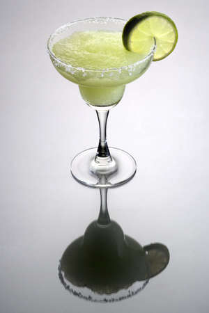 Frozen Margarita mixed drink with lime slice garnish on plain grey background with reflection photo