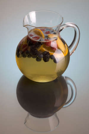 Pitcher of white wine sangria on grey background with reflection