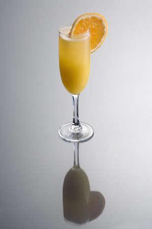 alcoholic beverages: Mimosa c�ctel con guarnici�n de rodaja de naranja sobre fondo gris con la reflexi�n  Foto de archivo