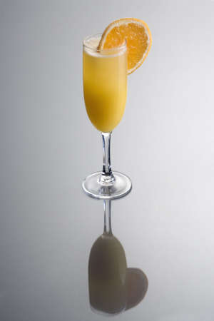 alcoholic drink: Mimosa mixed drink with orange slice garnish on grey background with reflection Stock Photo