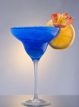 Blue Hawaiian mixed drink with orchid and orange garnish on plain background Stock Photo - 6390727