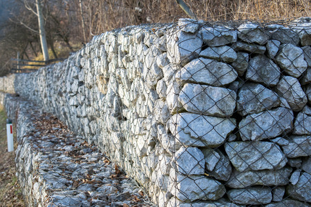 retaining: Retaining stone wall next to the road.Steel mesh of gabion wall.
