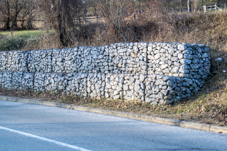 gabion mesh: Retaining stone wall next to the road.Steel mesh of gabion wall.