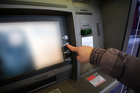 dial pad: Close up of hand entering pin at an ATM. Woman using banking machine.  Stock Photo