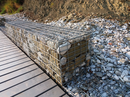 gabion mesh: Stones in metal wire cage - Steel mesh of gabion wall Stock Photo