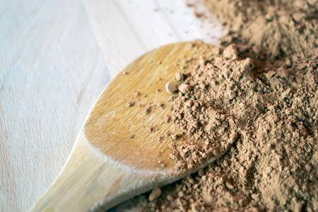 Pila de cacao en polvo aislado en el fondo de madera Foto de archivo - 87958738