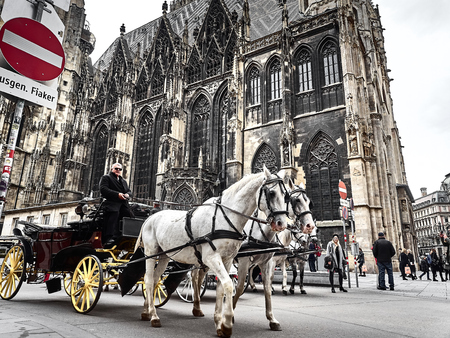 Vienna, Austria - November 1, 2018 - A horse-drawn carriage passing under the St. Stephens Cathedral in Vienna. Poeple are walking around to go shopping and visit the city Editorial