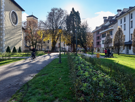 Shot of the park near the Église Notre Dame de Liesse, a Catholic Church in Annecy. The shot is taken during a sunny day. People are relaxing at the park Standard-Bild - 117735404
