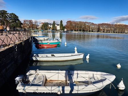 Annecy, France - December 07, 2018: Shot of the beautiful lake of Annecy full of parked boats. The shot is taken during a beautiful sunny day Standard-Bild - 117735409