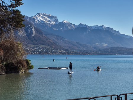 Annecy, France - December 07, 2018: Shot of the beautiful lake of Annecy and the mountains around. The shot is taken during a beautiful sunny day while people are practising water sports in the lake Standard-Bild - 117735413