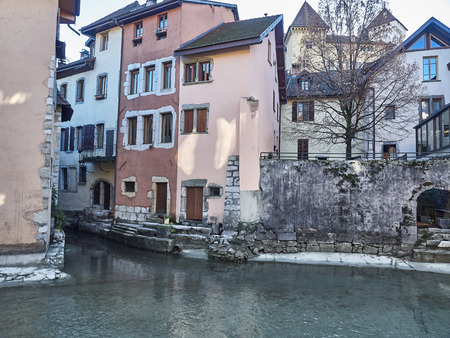 View of the colorful houses of Annecy reflecting into the water of the river Thiou during a sunny day Standard-Bild - 117775069