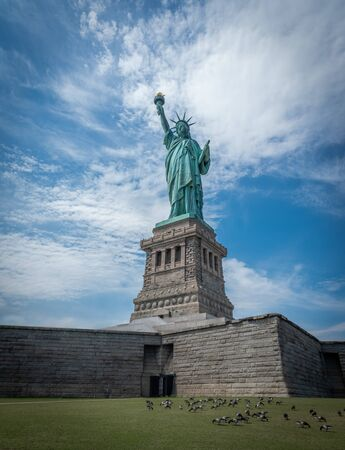 Shot of the Statue of Liberty in New York City, Usa. The shot is taken during a beautiful sunny day with a blue sky and white clouds in the background
