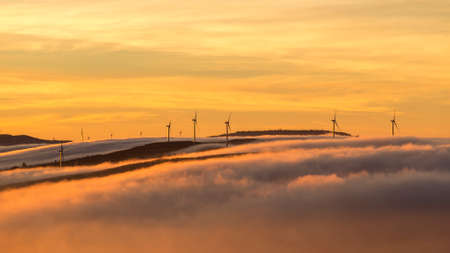 windy energy: wind turbines farm over clouds at sunrise morning