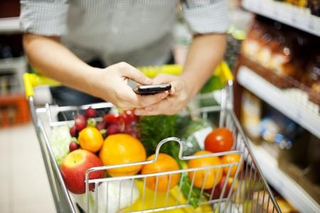carro supermercado: Hombre mensajes de texto durante las compras