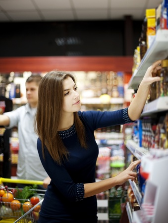 Young woman trying make a choice in supermarket photo