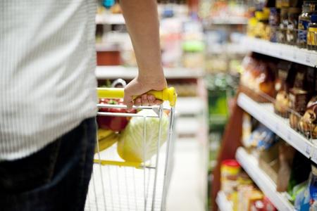 hombre empujando: El hombre empujando carrito de la compra