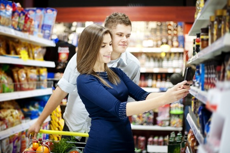 grocery cart: Young couple shopping at supermarket