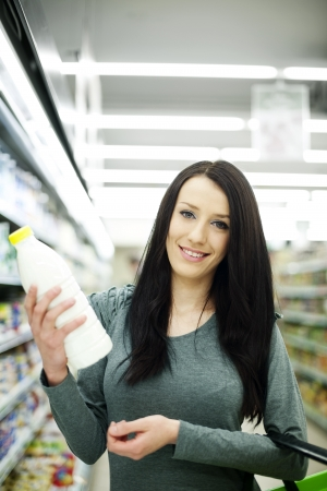 Woman choosing bottle of milk at supermarket Stock Photo - 18161920