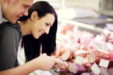 butcher s shop: Young couple in butchers shop Stock Photo