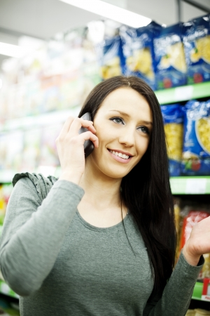 Beautiful woman on mobile phone at supermarket Stock Photo - 18161952
